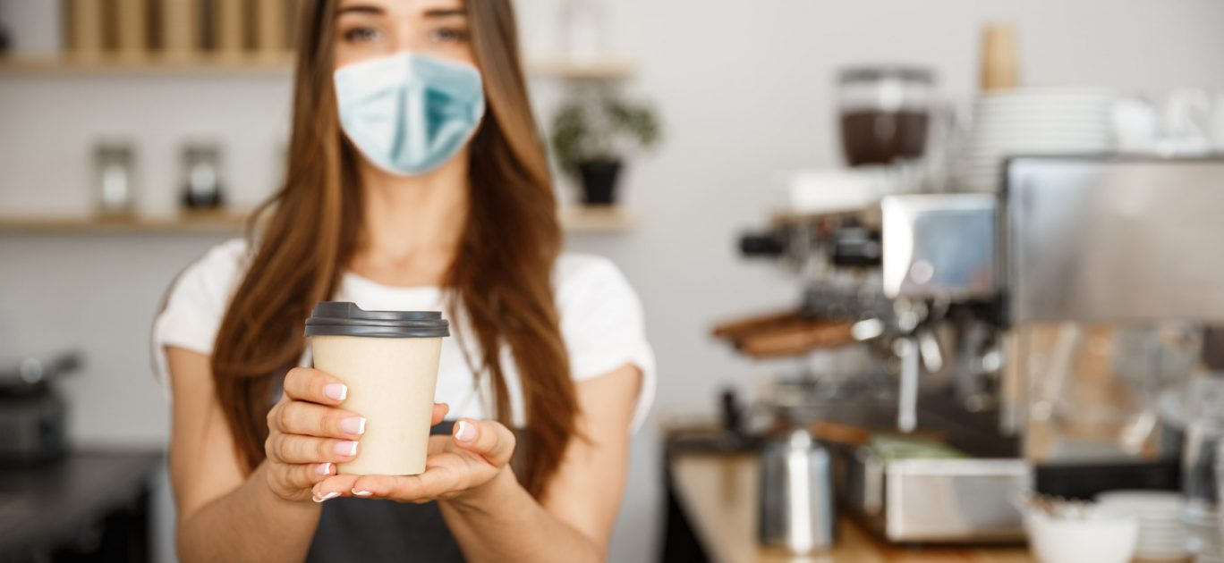 Business Owner Concept - Beautiful Caucasian Barista in face mask offers disposable take away hot coffee at the modern coffee shop.
